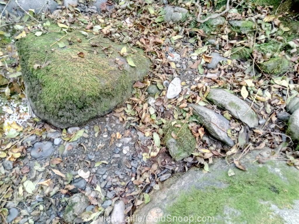 Sable noir et paillettes d'or, en aval et en dessous d'un gros rocher, au pied d'une terrasse