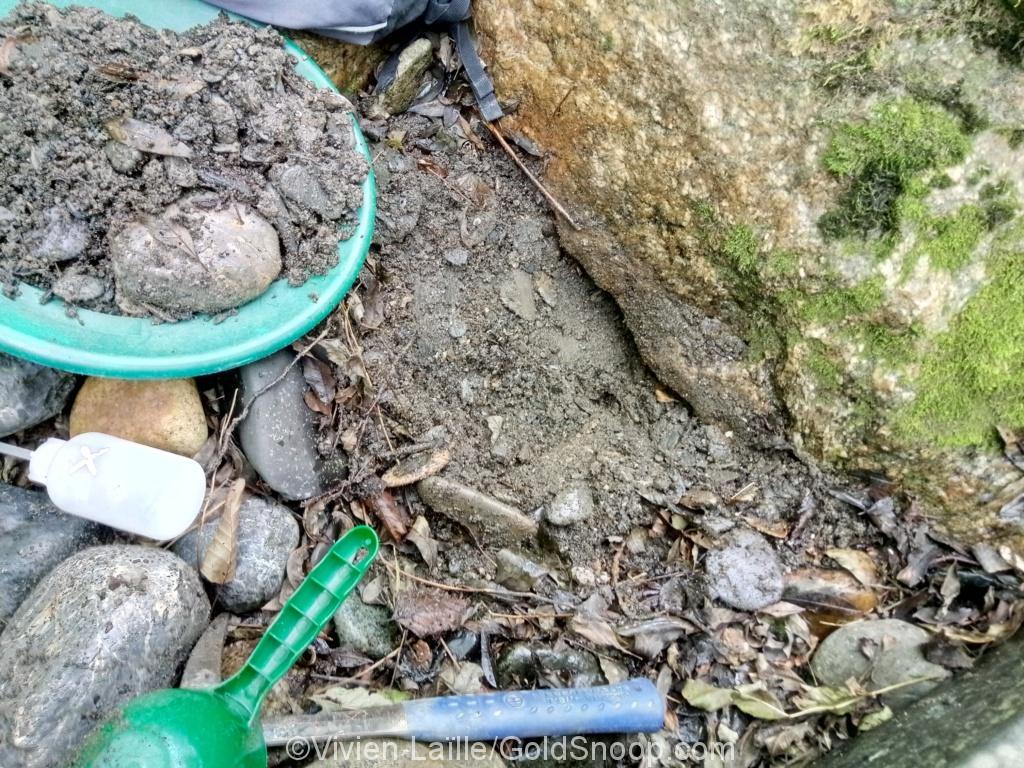 Des paillettes d'or sous 2 gros rochers ovales dans un placier alluvionnaire